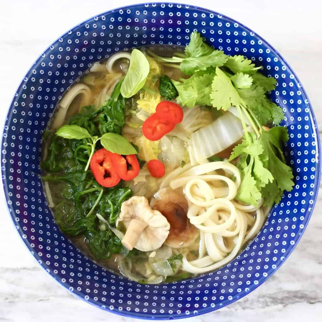 Photo of a blue bowl with noodle soup and vegetables against a marble background