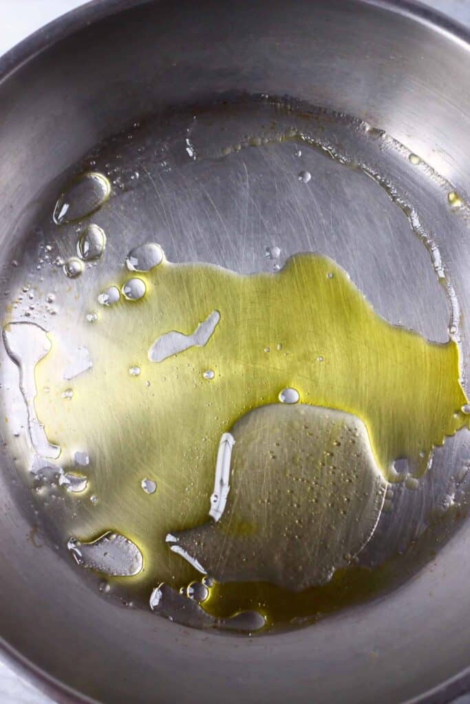 A silver frying pan with water, oil and agave syrup