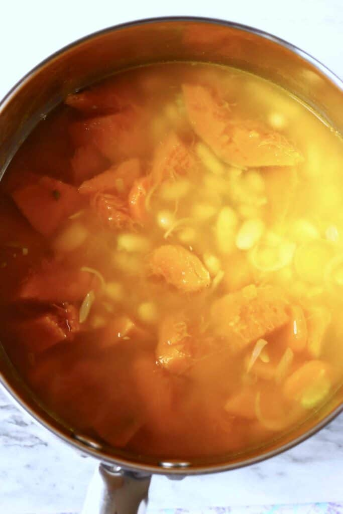Photo of pumpkin pieces and white beans in a silver saucepan covered with broth