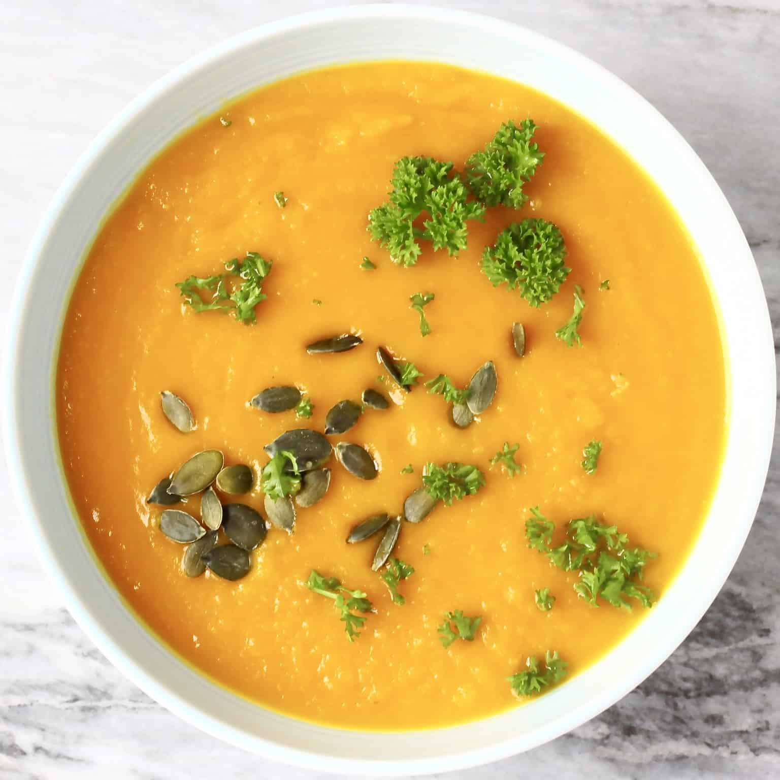 Photo of smooth orange pumpkin soup topped with green pumpkin seeds and curly parsley in a light blue bowl against a marble background
