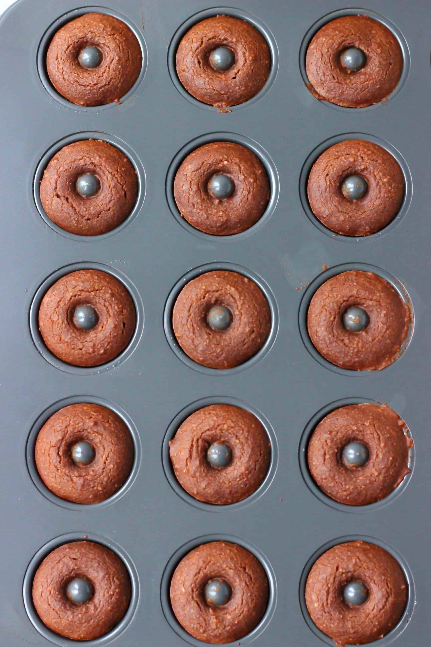 Cooked chocolate donuts in a mini donut tin