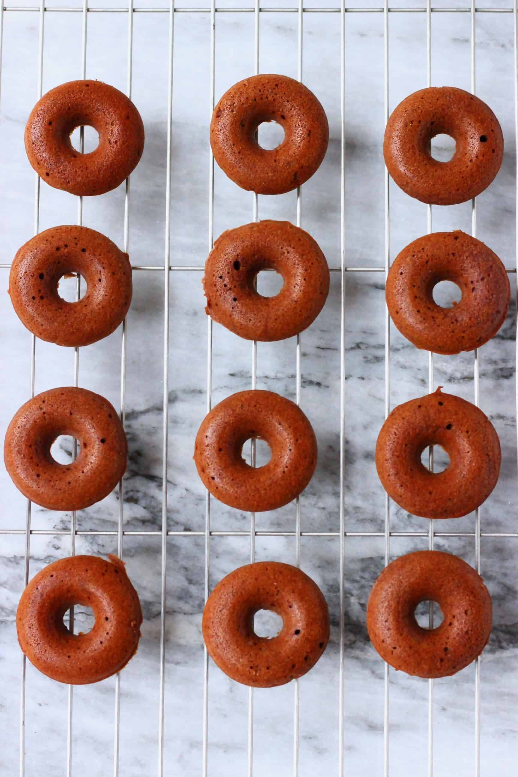 Chocolate mini donuts on a wire rack against a marble background
