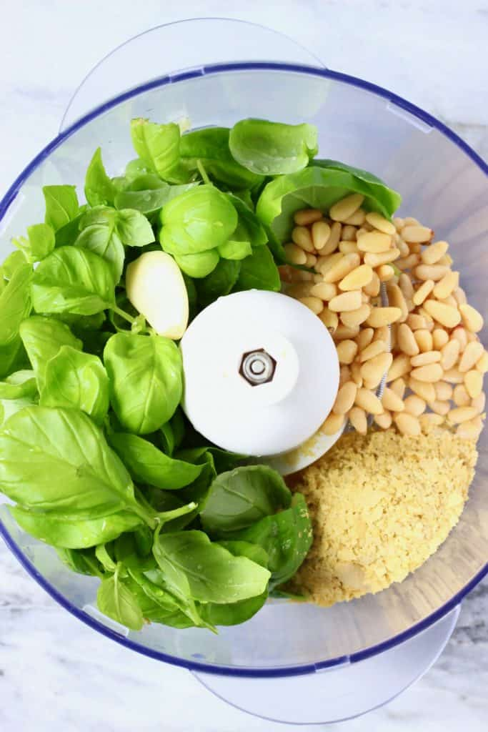Fresh basil, garlic, nutritional yeast and pine nuts in a food processor against a marble background