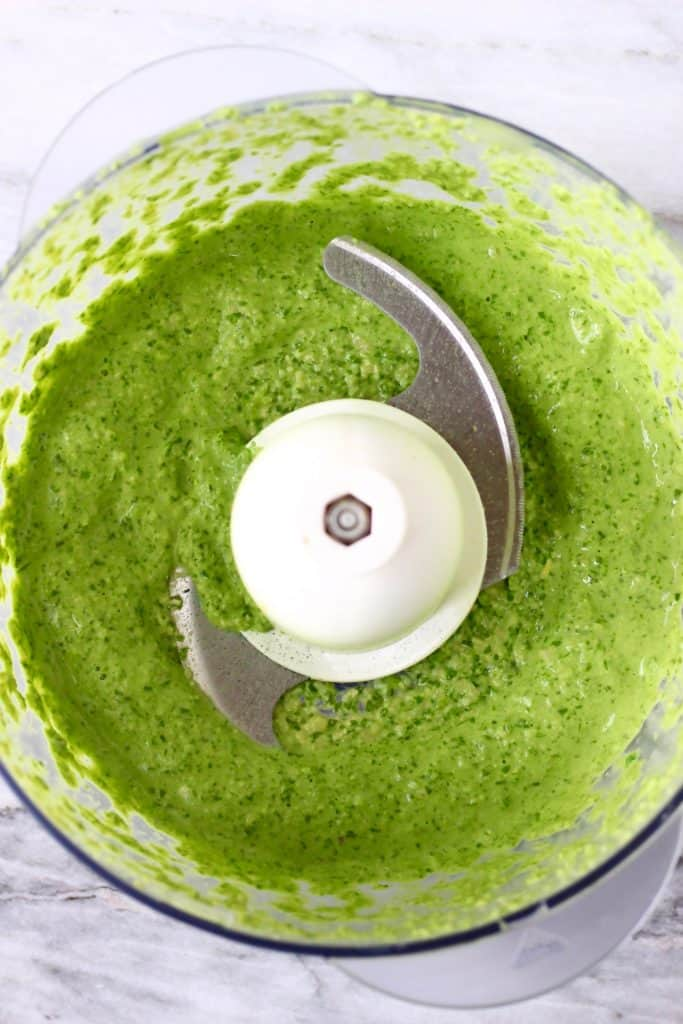 Green pesto in a food processor against a marble background