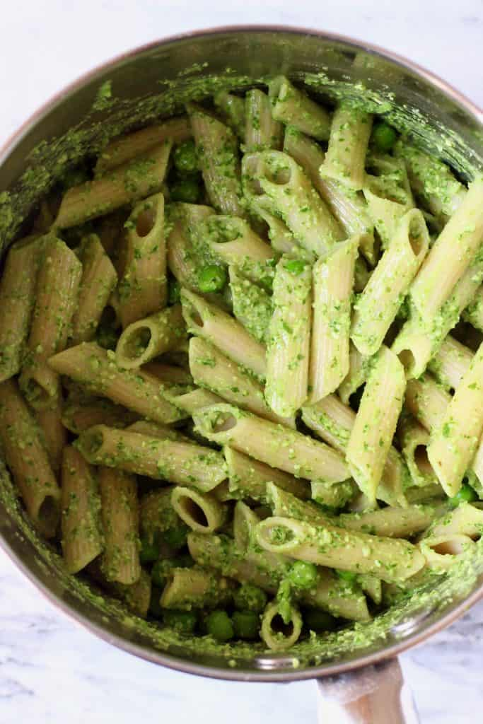 Cooked penne pasta and green peas in a silver saucepan with green pesto