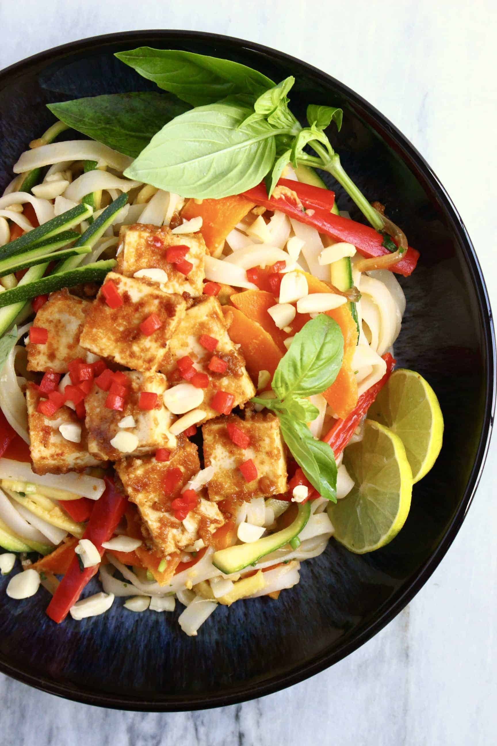 Vegan tofu pad Thai with vegetables and herbs and chopped peanuts in a black bowl