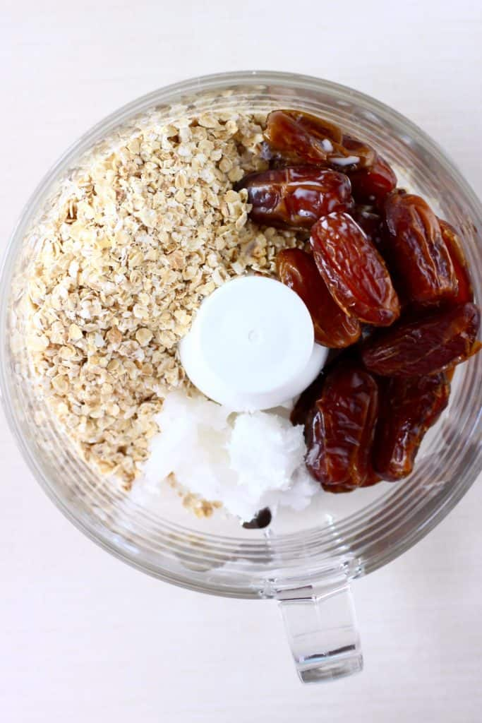 Oats, dates and coconut oil in a food processor against a white background