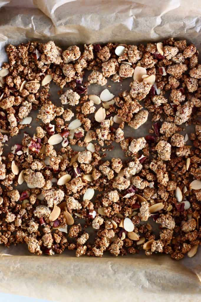 Brown granola with flaked almonds and pecan nuts on a baking tray lined with brown baking paper