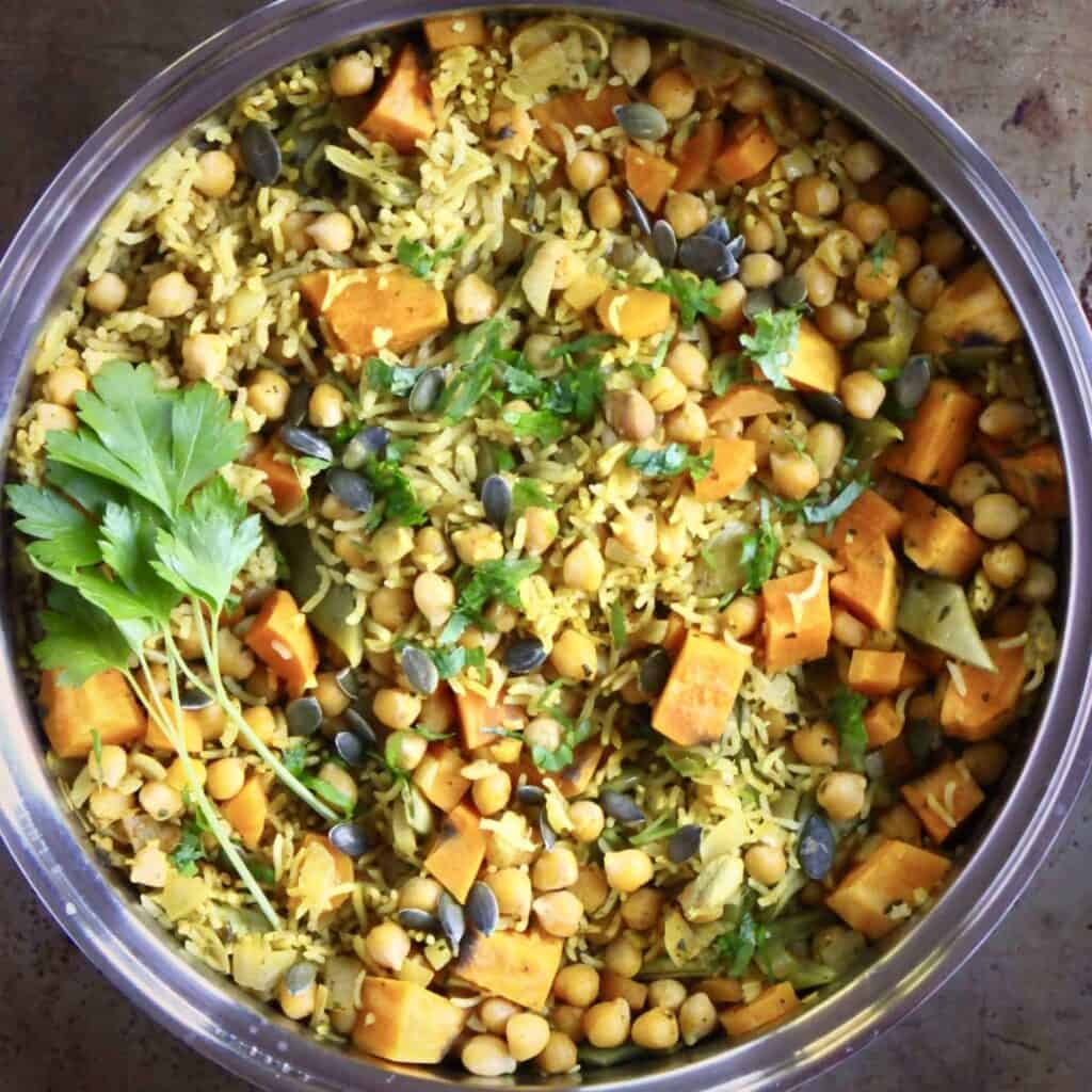 Photo of yellow biryani rice with chopped pumpkin, chickpeas and pumpkin seeds in a silver saucepan