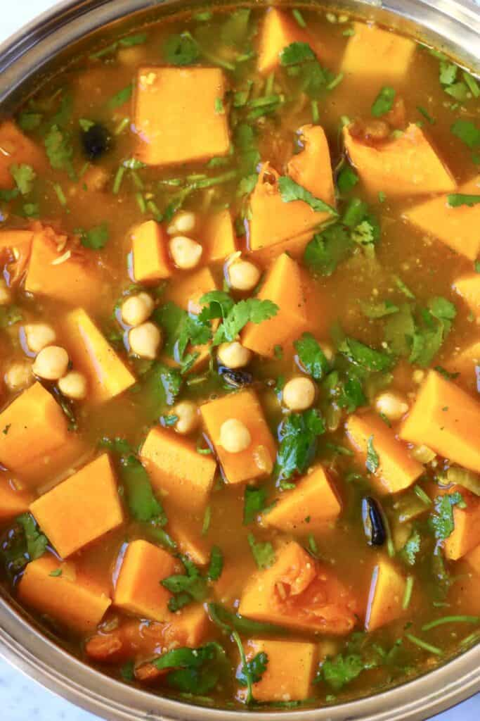 Photo of chickpeas, diced pumpkin and coriander in water in a silver frying pan