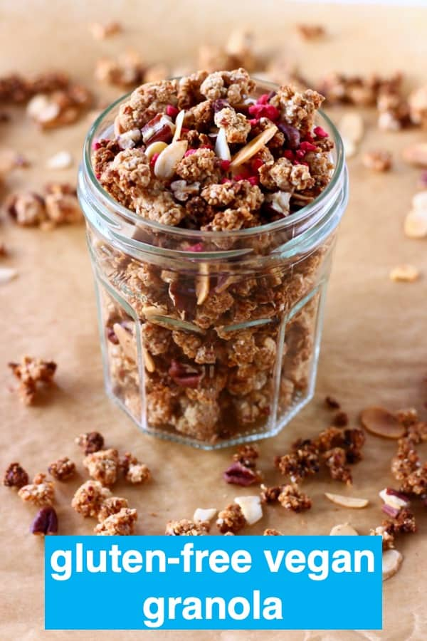 Granola with pecan nuts and flaked almonds in a glass jar on a sheet of brown baking paper scattered with granola pieces