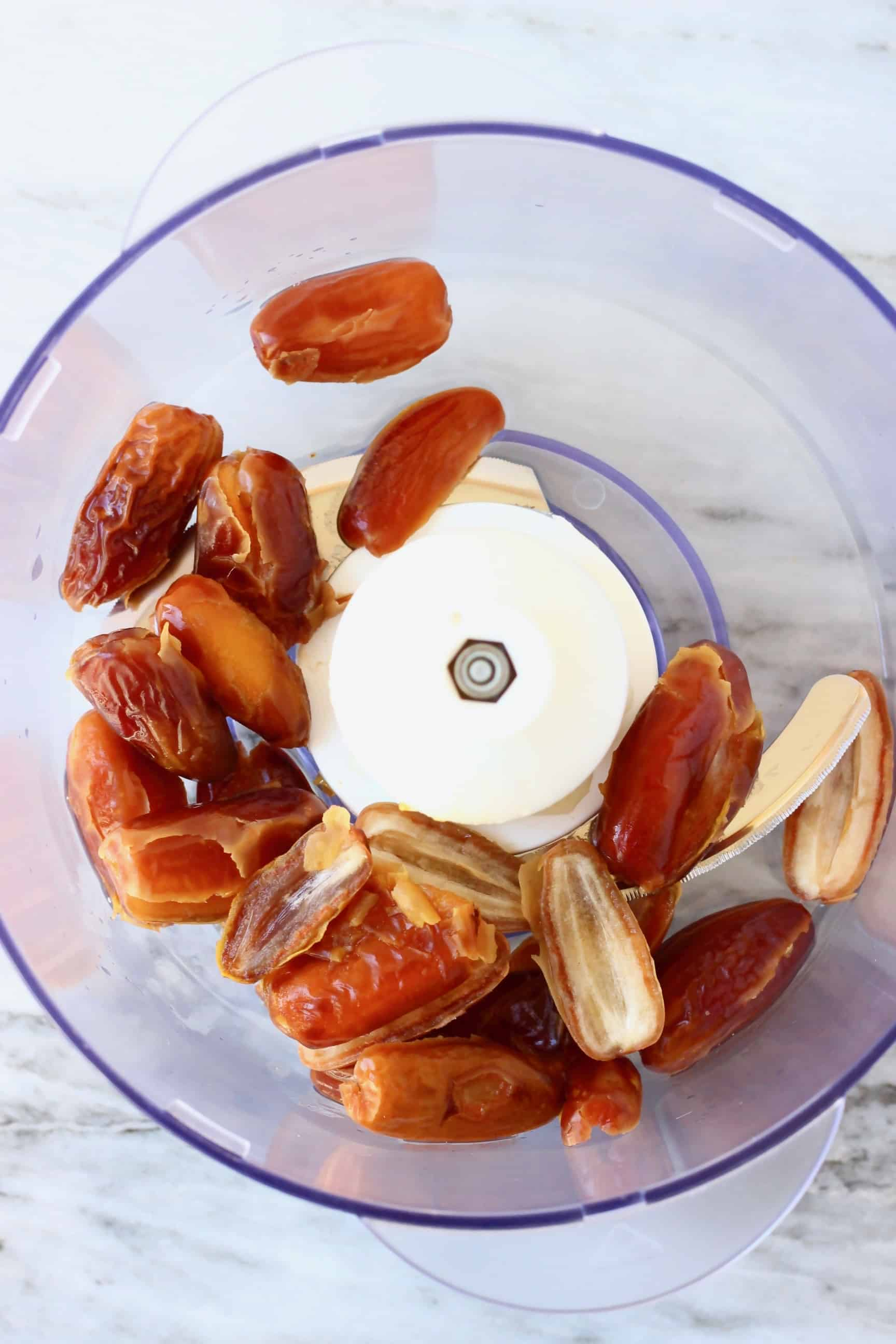 Dates in a food processor against a marble background