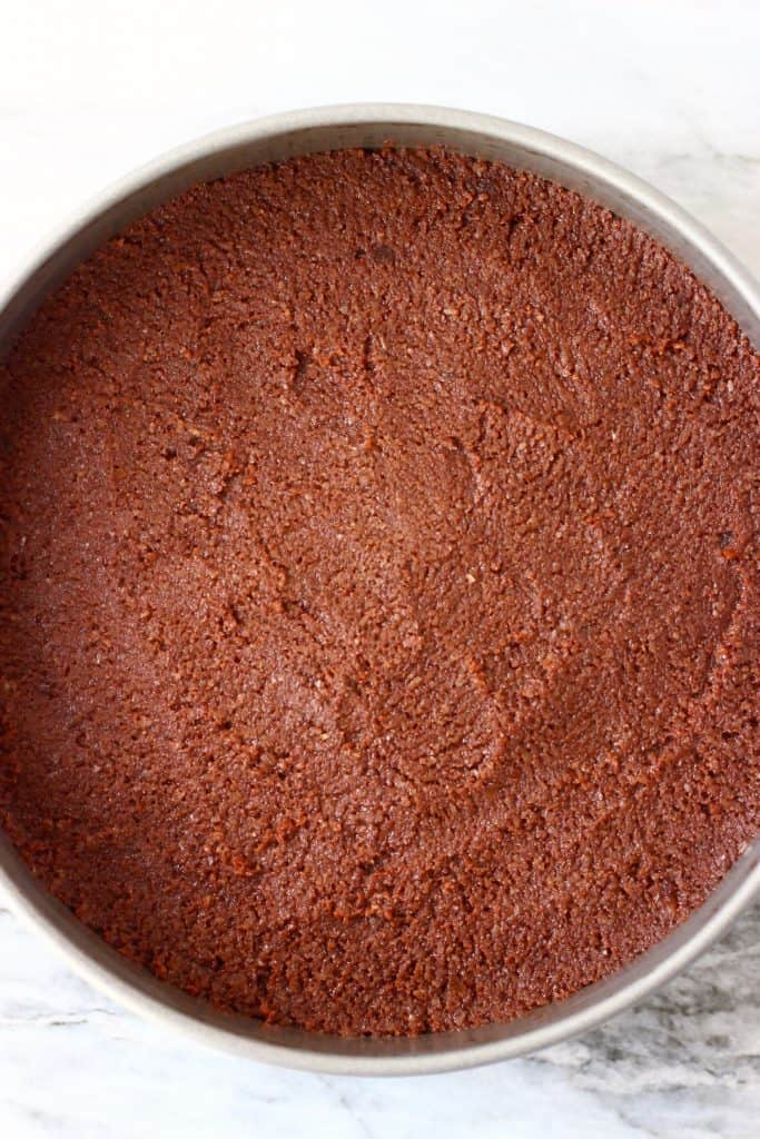 Raw chocolate cake batter in a silver baking tin against a marble background