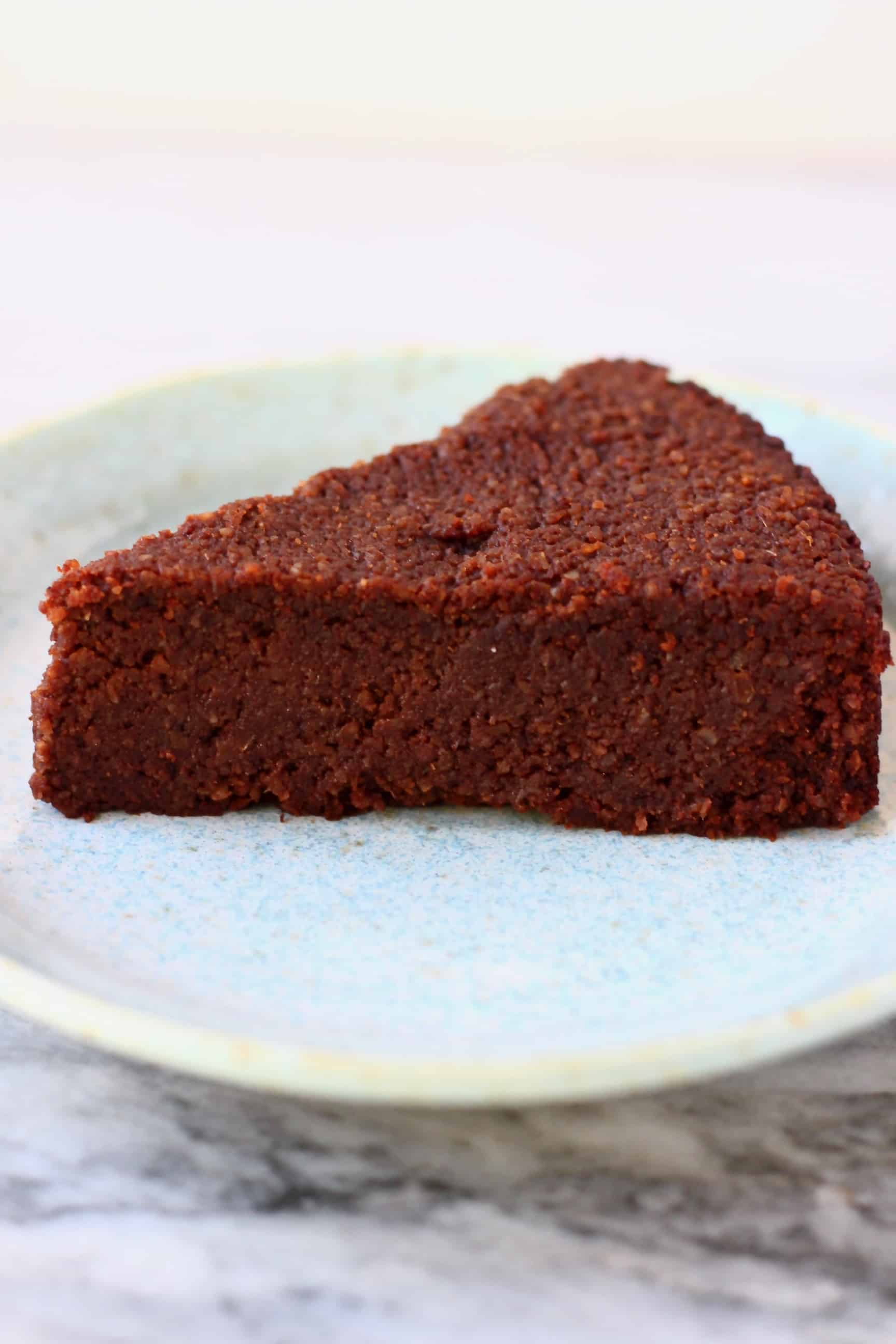 A slice of gluten-free vegan chocolate torte on a blue plate against a marble background