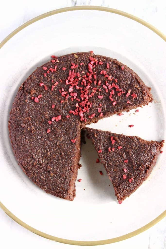 A chocolate cake covered in freeze-dried raspberries on a white plate