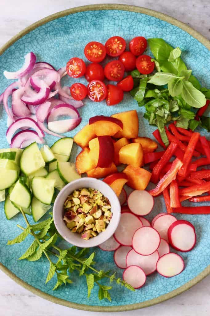 Lots of different fruits and vegetables cut up and laid out on a blue plate against a marble background