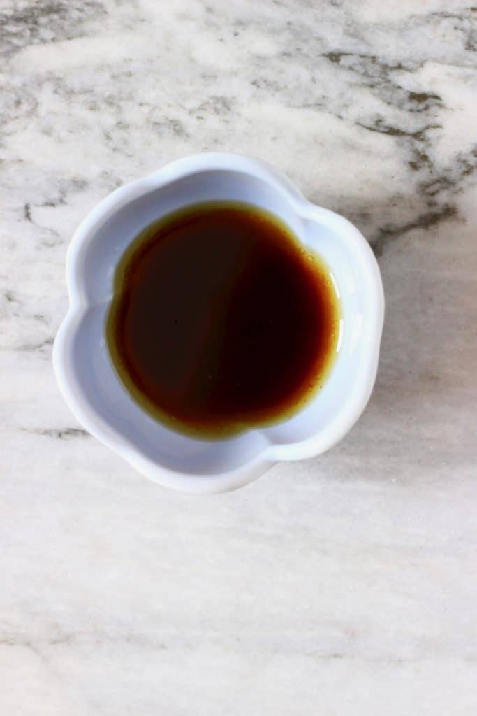 A small light blue bowl filled with dark brown dressing against a marble background