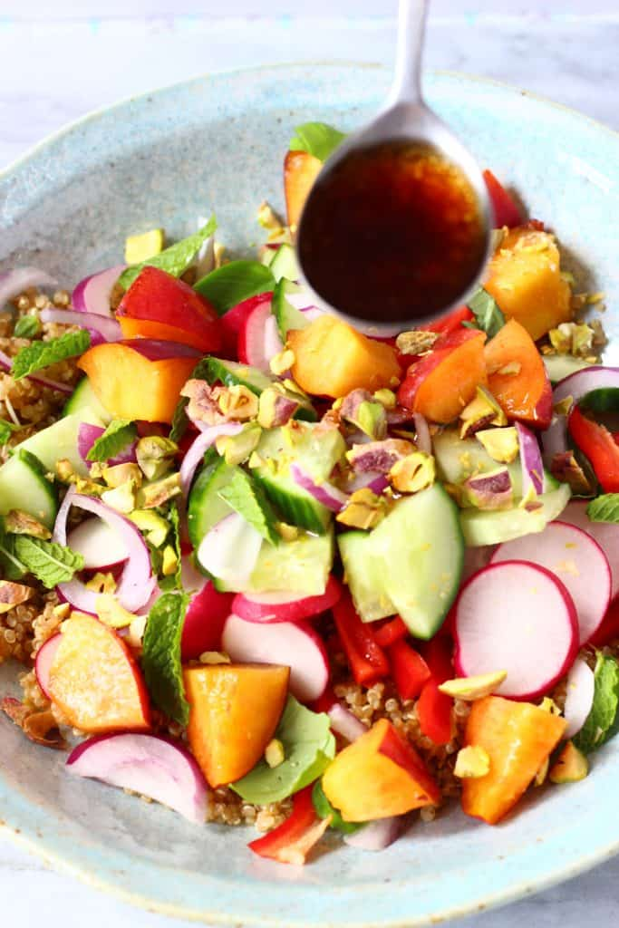 Cooked quinoa with lots of different chopped fruit and vegetables in a light blue bowl with a silver spoon pouring over a dark brown dressing against a marble background