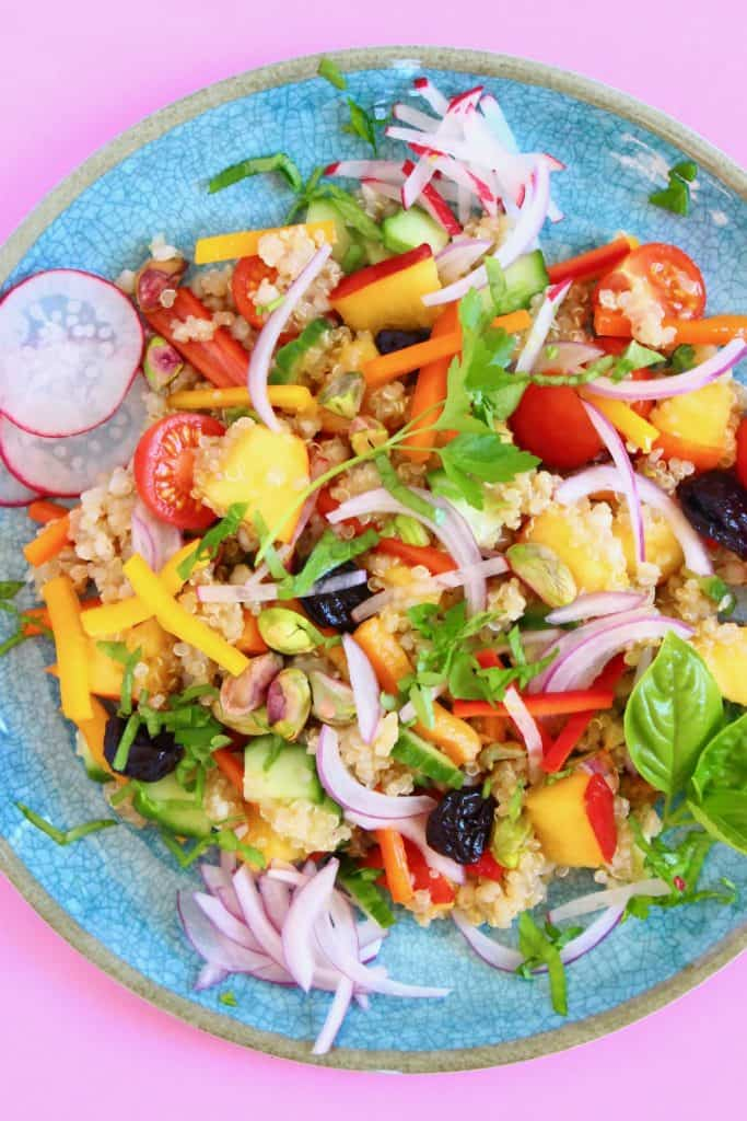 Quinoa salad with nectarine, dried cherries, sliced red onion and herbs on a blue plate against a pink background