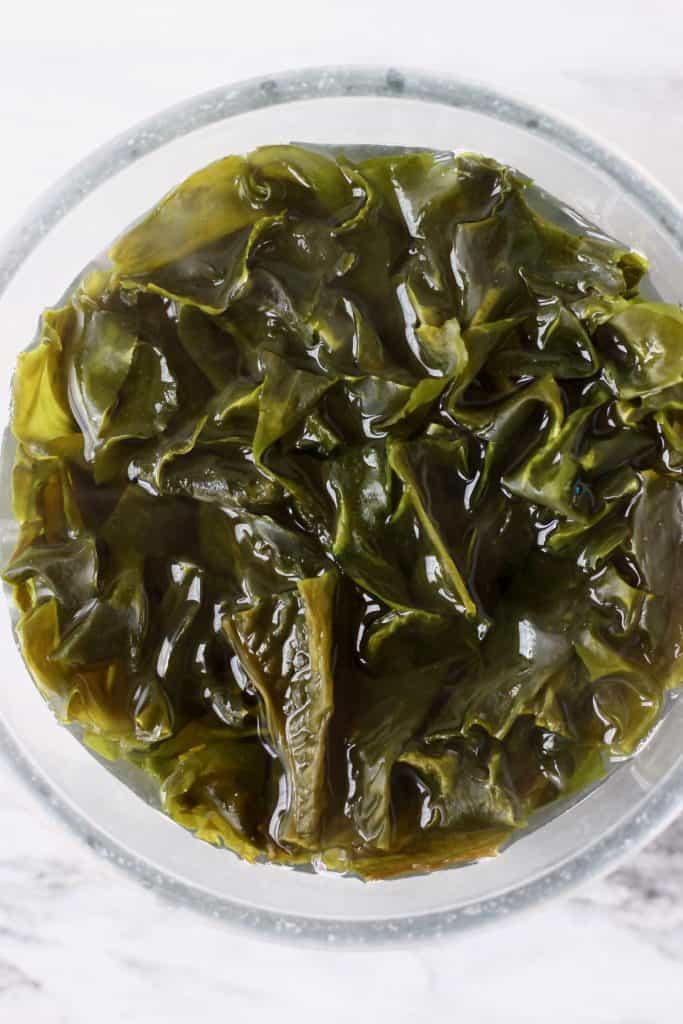 Wakame seaweed soaking in water in a glass bowl against a marble background