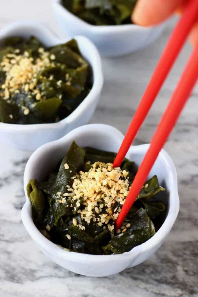 Seaweed salad topped with sesame seeds in three small blue bowls against a marble background with a pair of red chopsticks stuck in one of the bowls