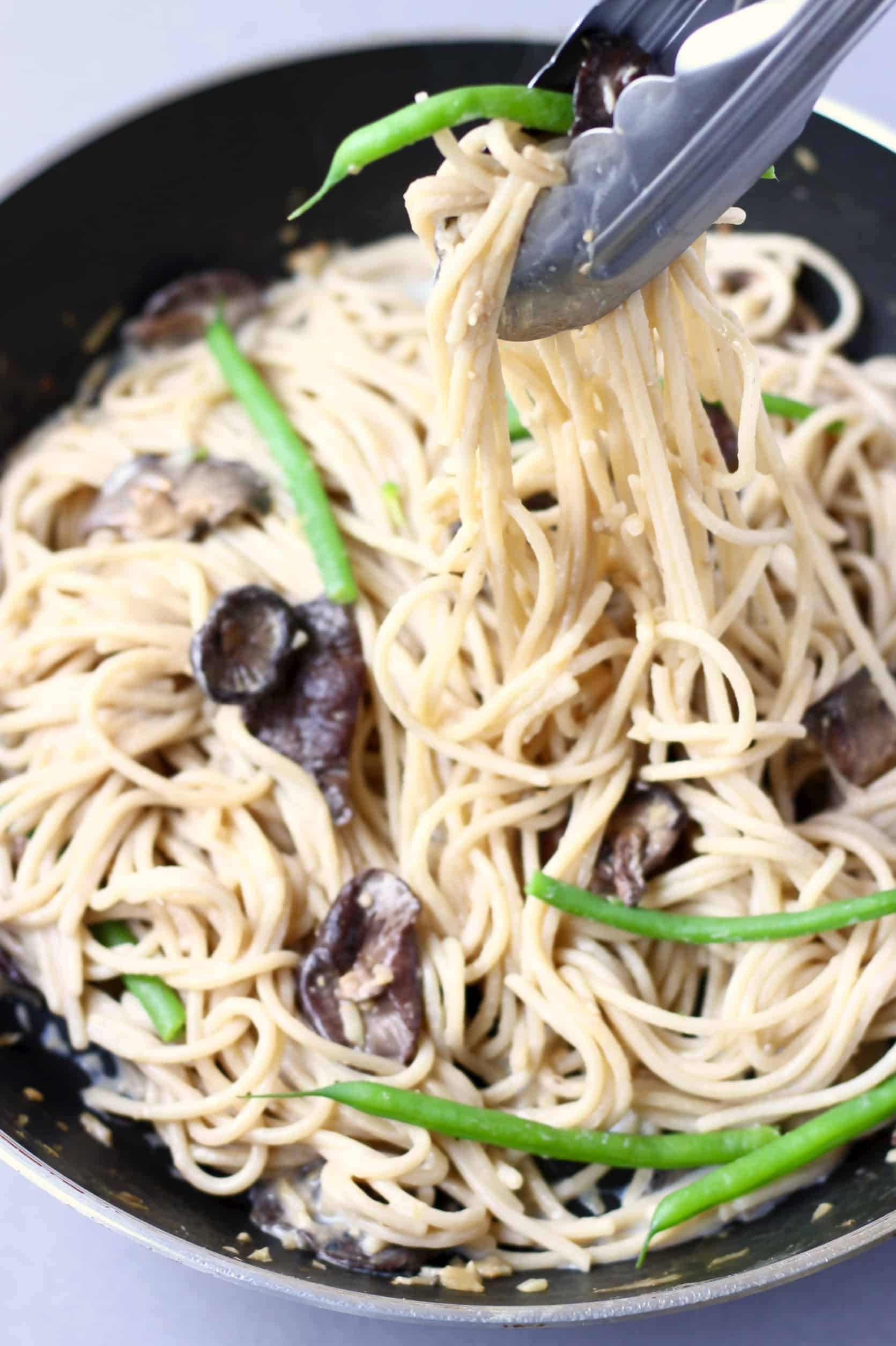 Spaghetti with creamy vegan miso pasta sauce, shiitake mushrooms and French beans being lifted up with tongs in a black frying pan