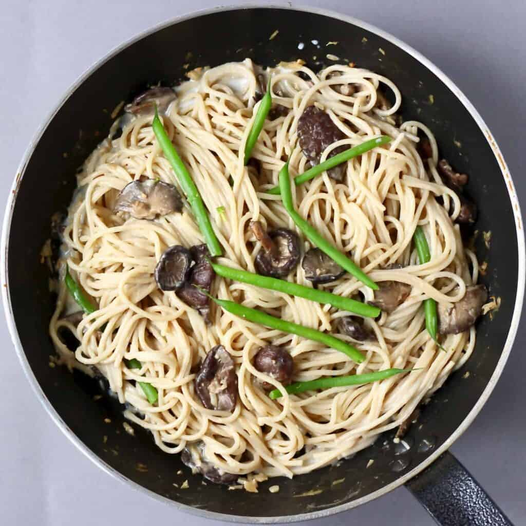 Photo of a black saucepan with spaghetti, mushrooms and green beans