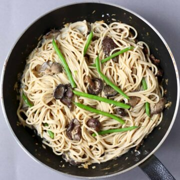Spaghetti with creamy vegan miso pasta sauce, shiitake mushrooms and French beans in a black frying pan