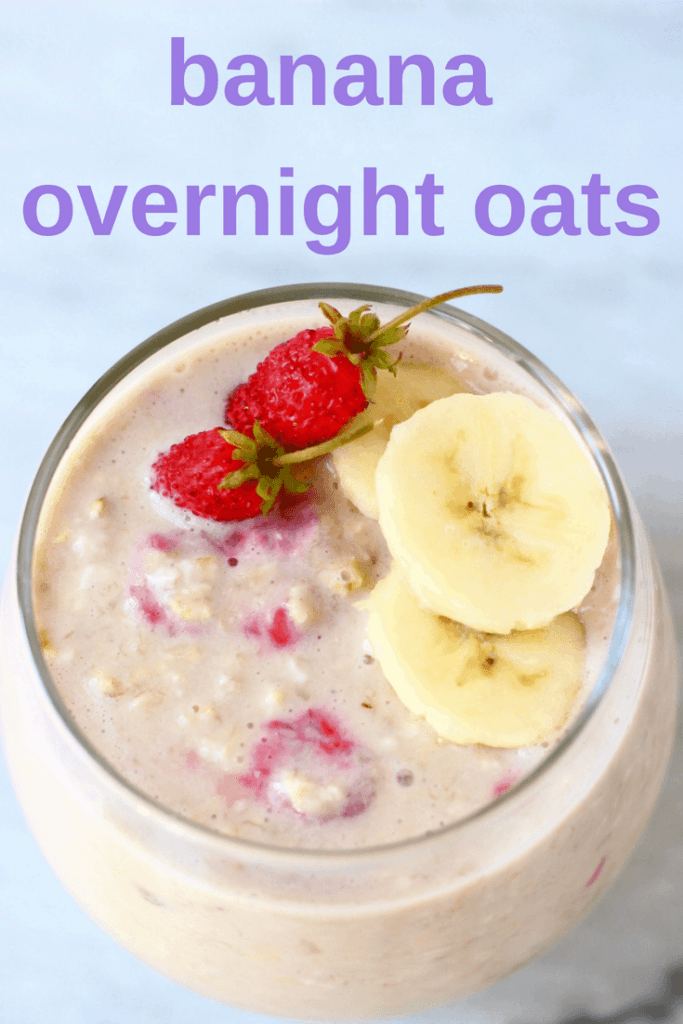 Photo of overnight oats in a glass cup topped with sliced bananas and mini strawberries