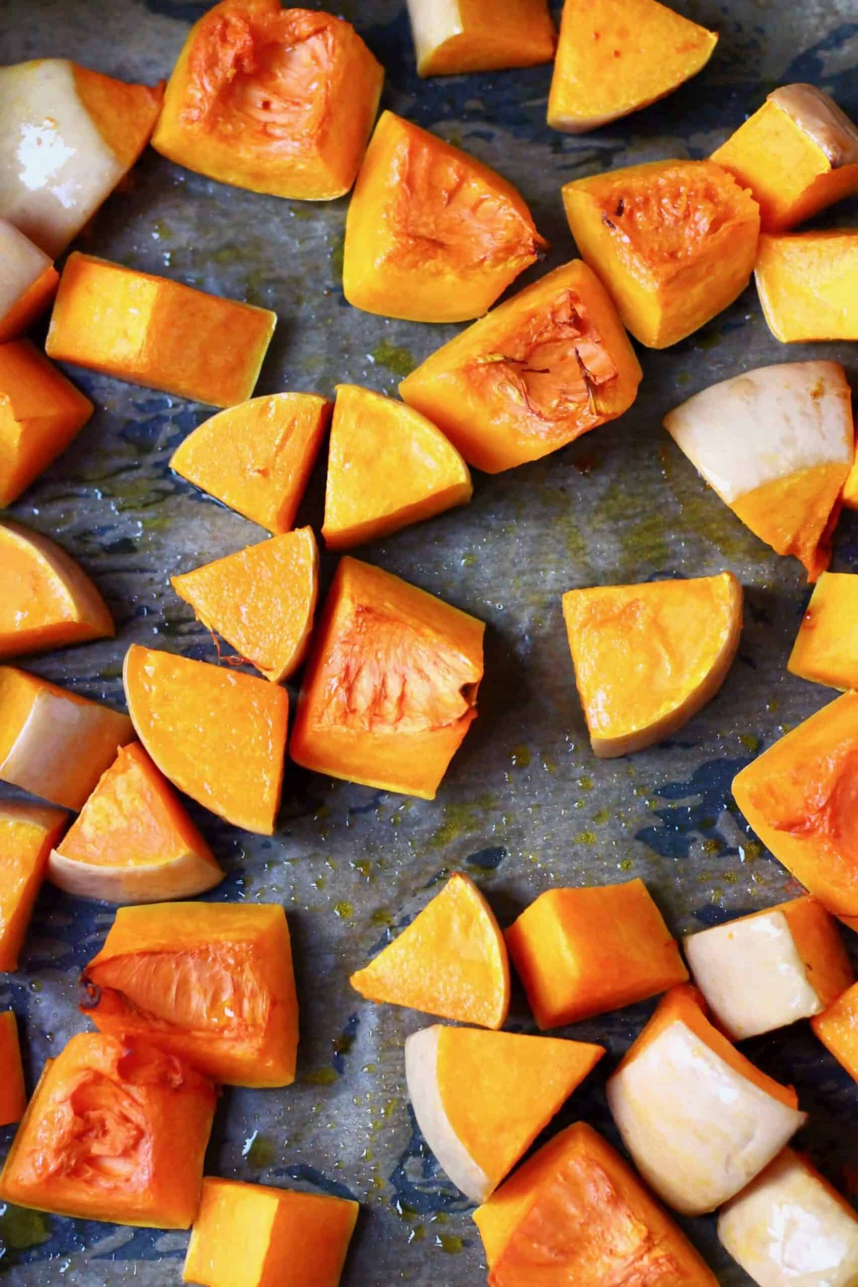 Pieces of roasted pumpkin on a baking tray lined with baking paper
