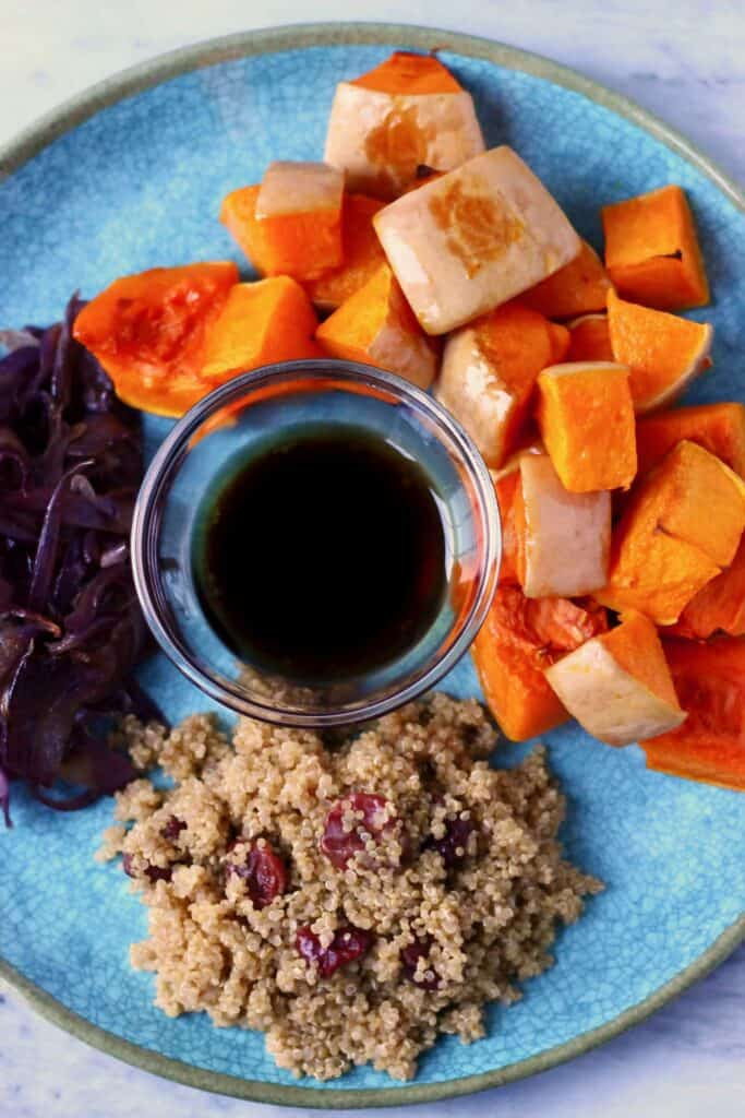 Photo of roasted pumpkin pieces, fried red onion, cooked quinoa and a small bowl of black dressing on a blue plate