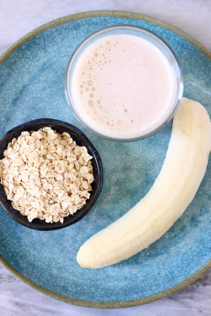 Photo of a blue plate against a marble background topped with oats, a peeled banana and a cup of milk