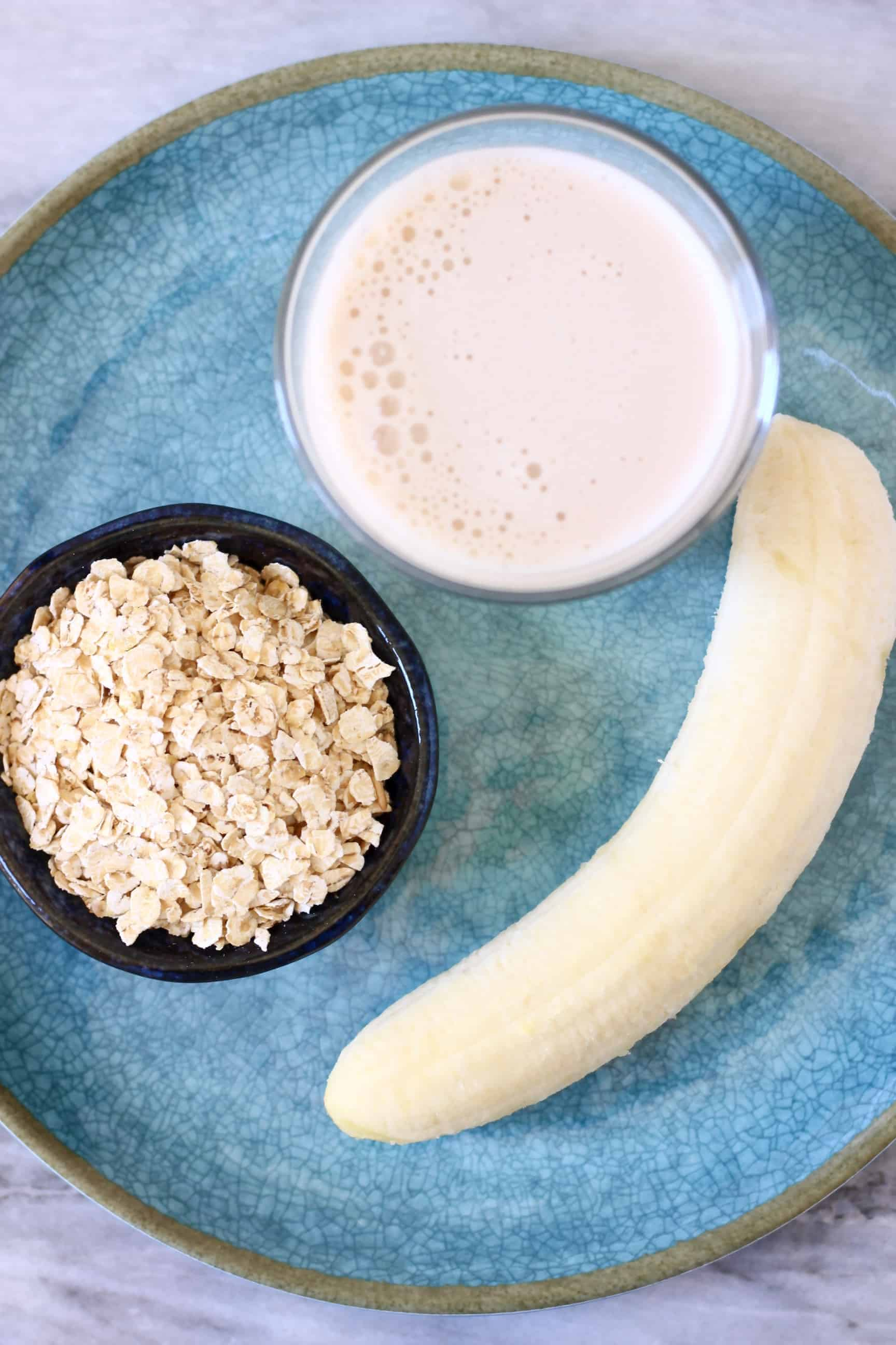 Oats, a peeled banana and a cup of almond milk on a blue plate