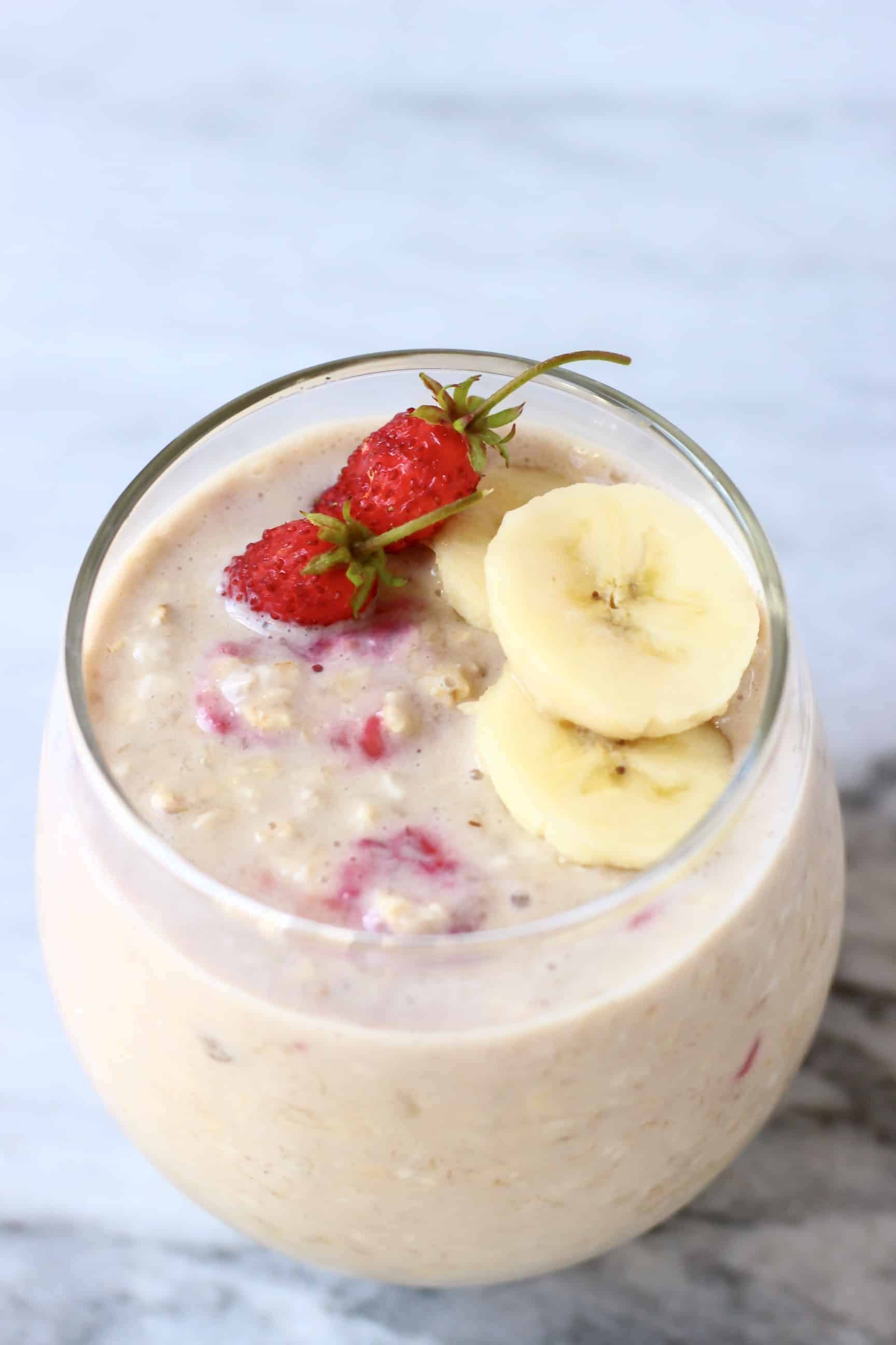 Banana overnight oats in a glass cup topped with sliced bananas and mini strawberries