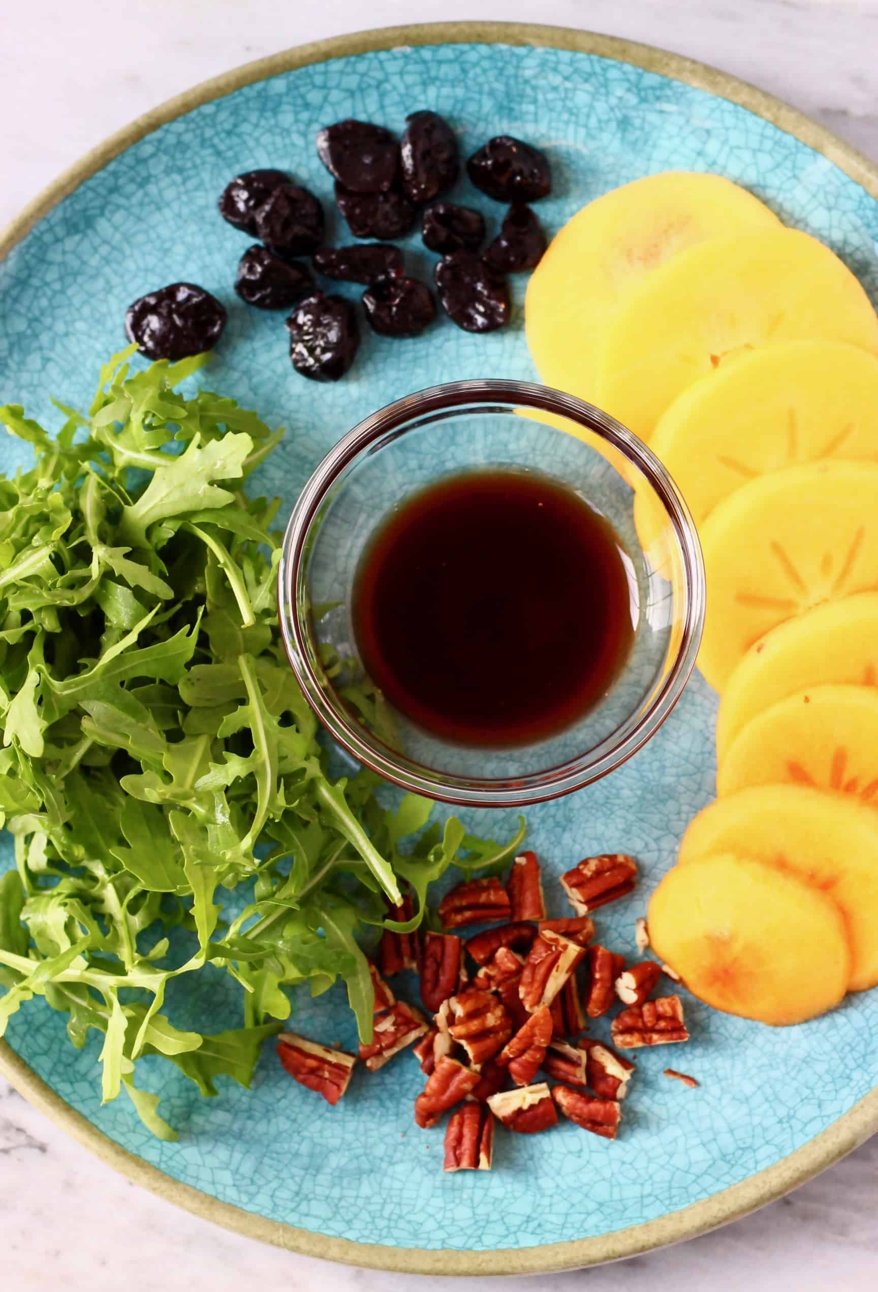 Persimmon slices, dried cherries, rocket, chopped pecan nuts and a brown dressing in a bowl on a plate