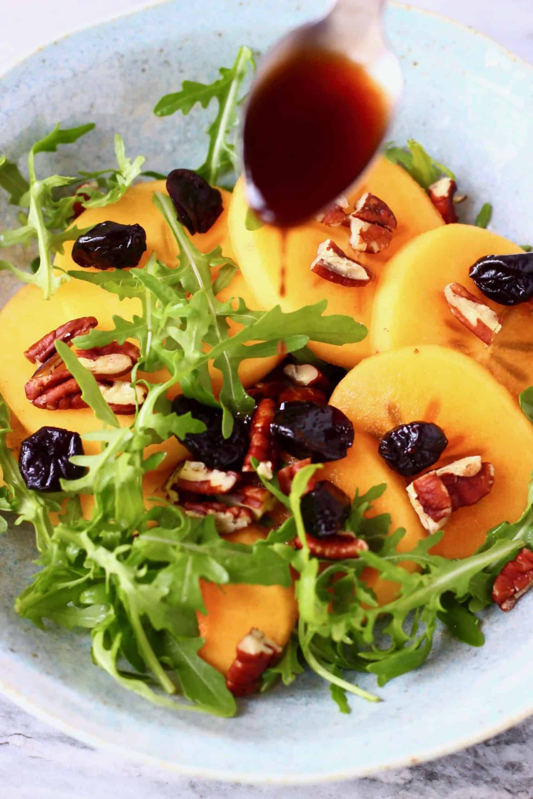 Persimmon salad with sliced persimmon, dried cherries, chopped pecan nuts and rocket in a bowl with a spoon pouring brown dressing over it