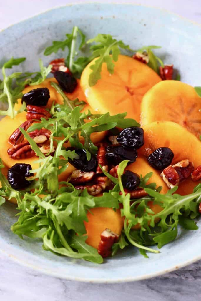 Photo of persimmon salad in a blue bowl against a marble background