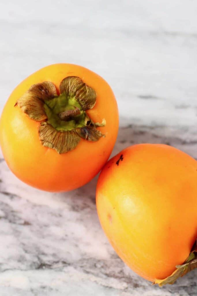 Photo of two persimmons on a marble background