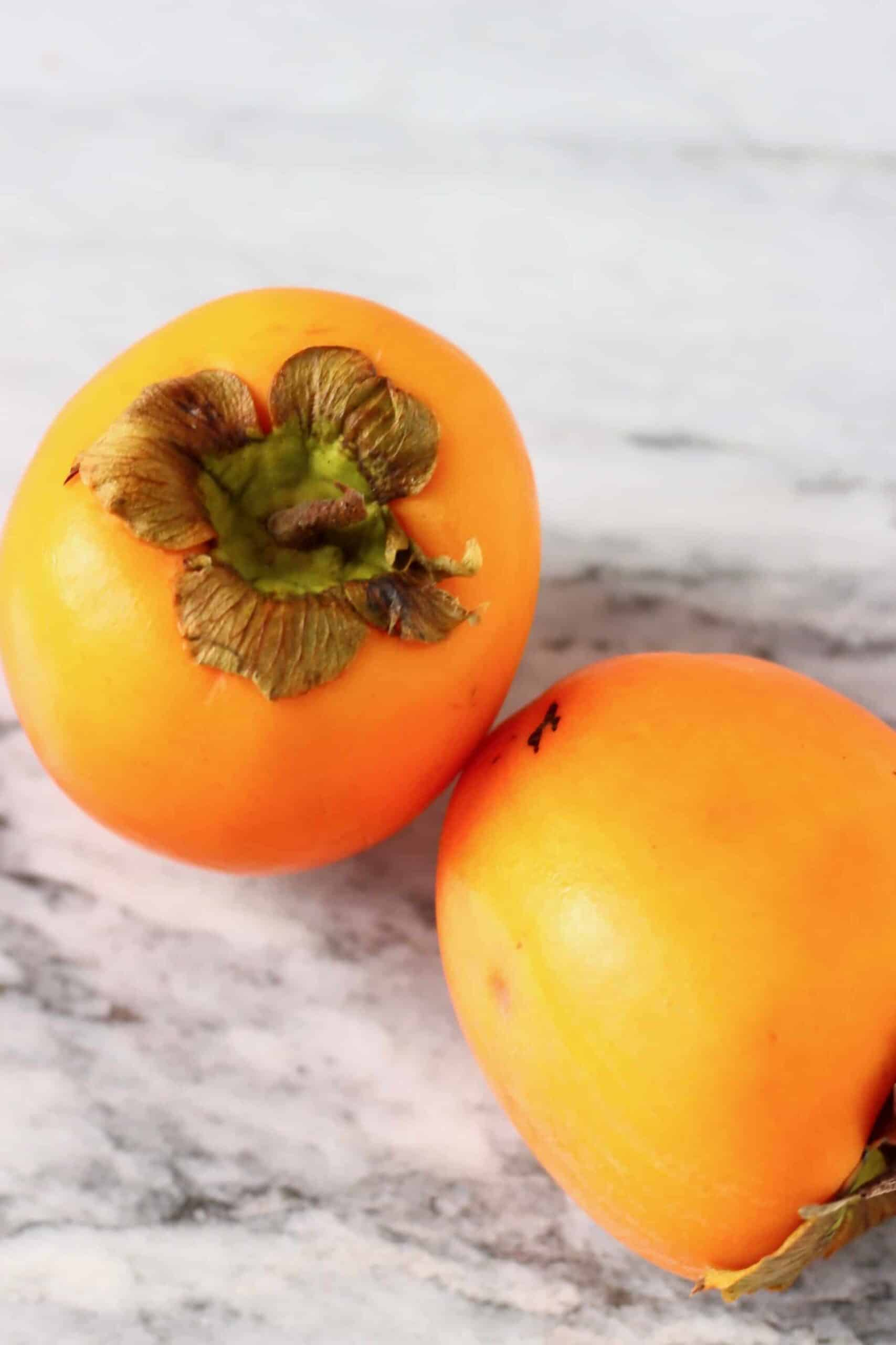 Two persimmons on a marble background
