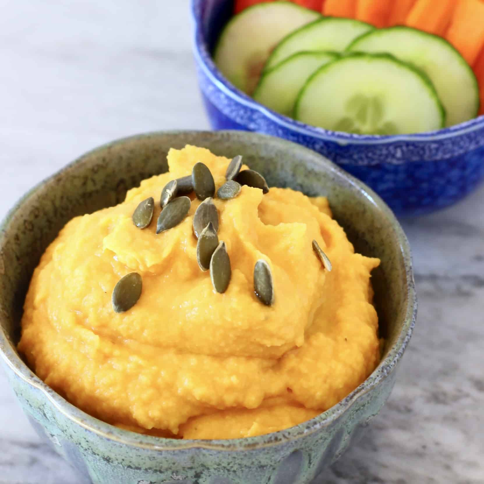 Photo of a grey bowl of orange pumpkin hummus topped with green pumpkin seeds and a blue bowl of chopped vegetables on a marble surface