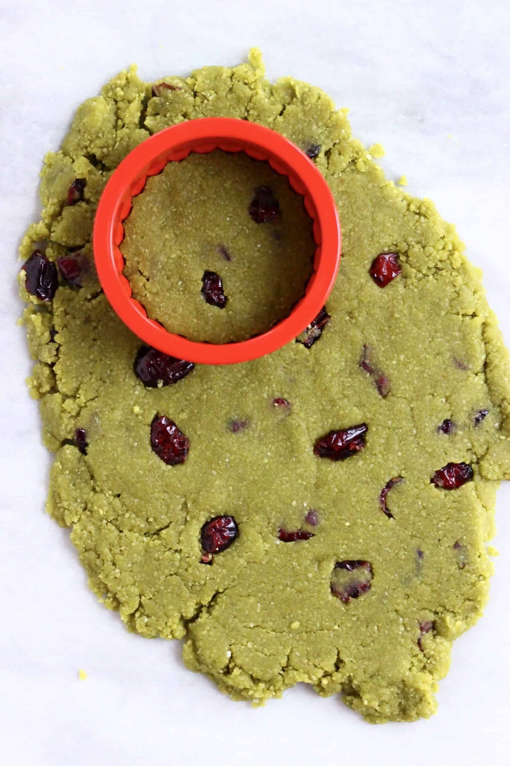 Raw vegan matcha shortbread cookie dough with dried cranberries rolled out on a baking sheet with a round cookie cutter on it