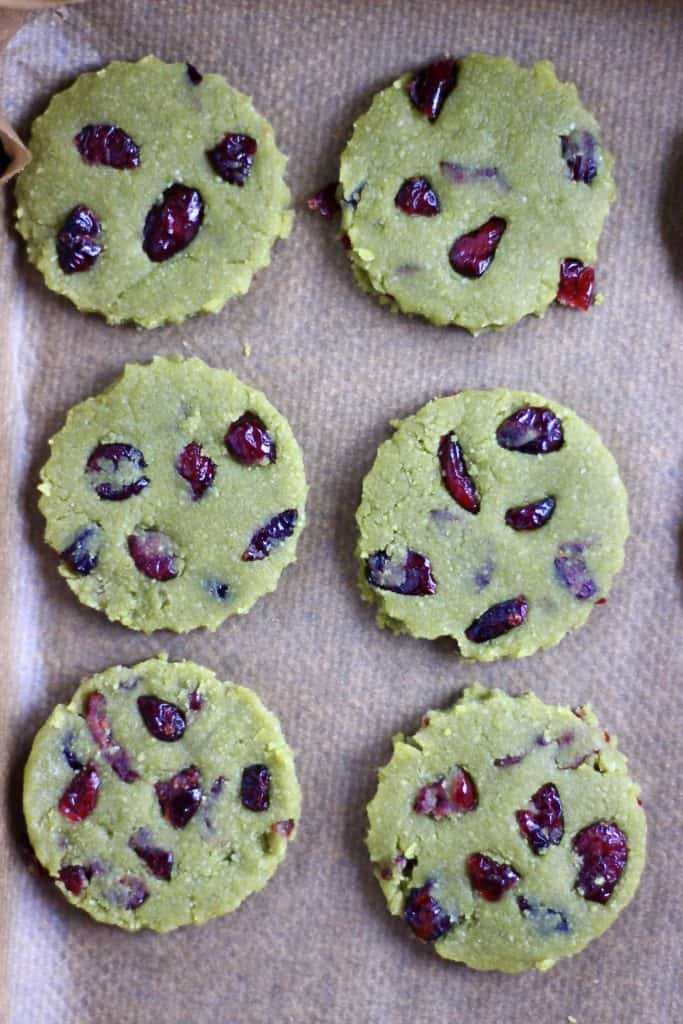 Six raw matcha cookies with dried cranberries on a baking tray