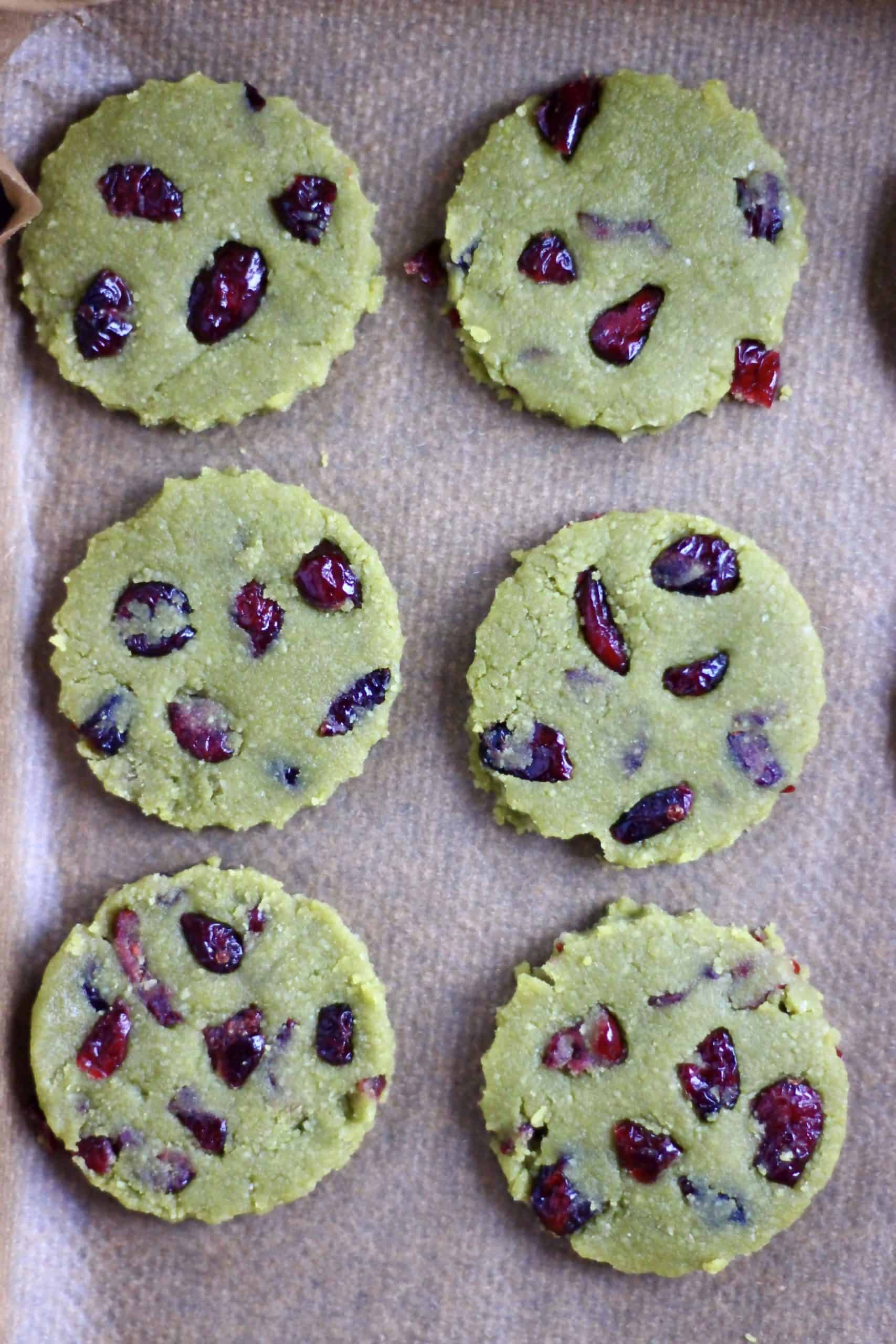 Six raw vegan matcha shortbread cookies with dried cranberries on a baking tray lined with baking paper