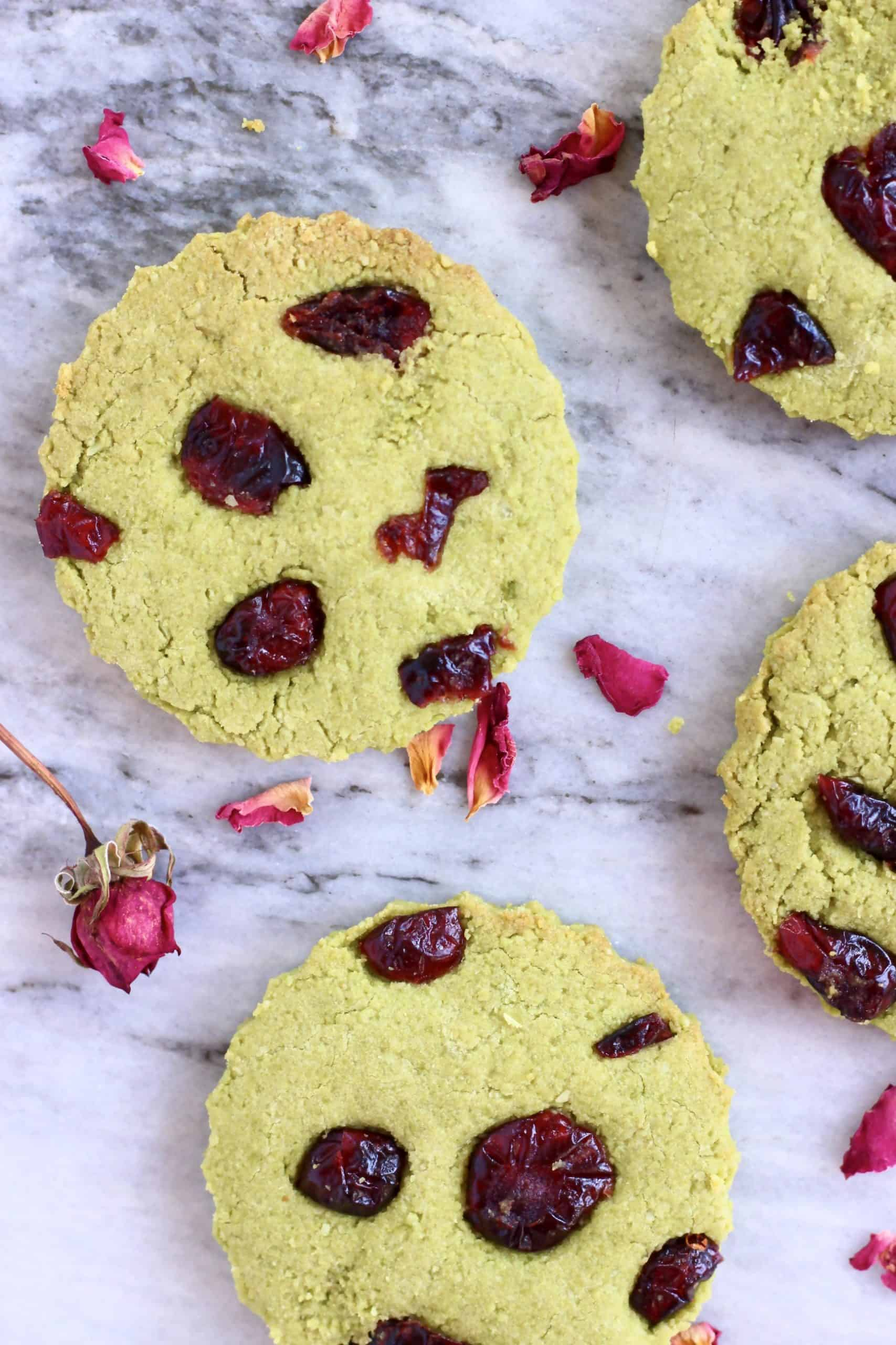 Four vegan matcha shortbread cookies with dried cranberries on a marble background