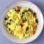 Photo of yellow rice with vegetables in a ceramic bowl against a grey background