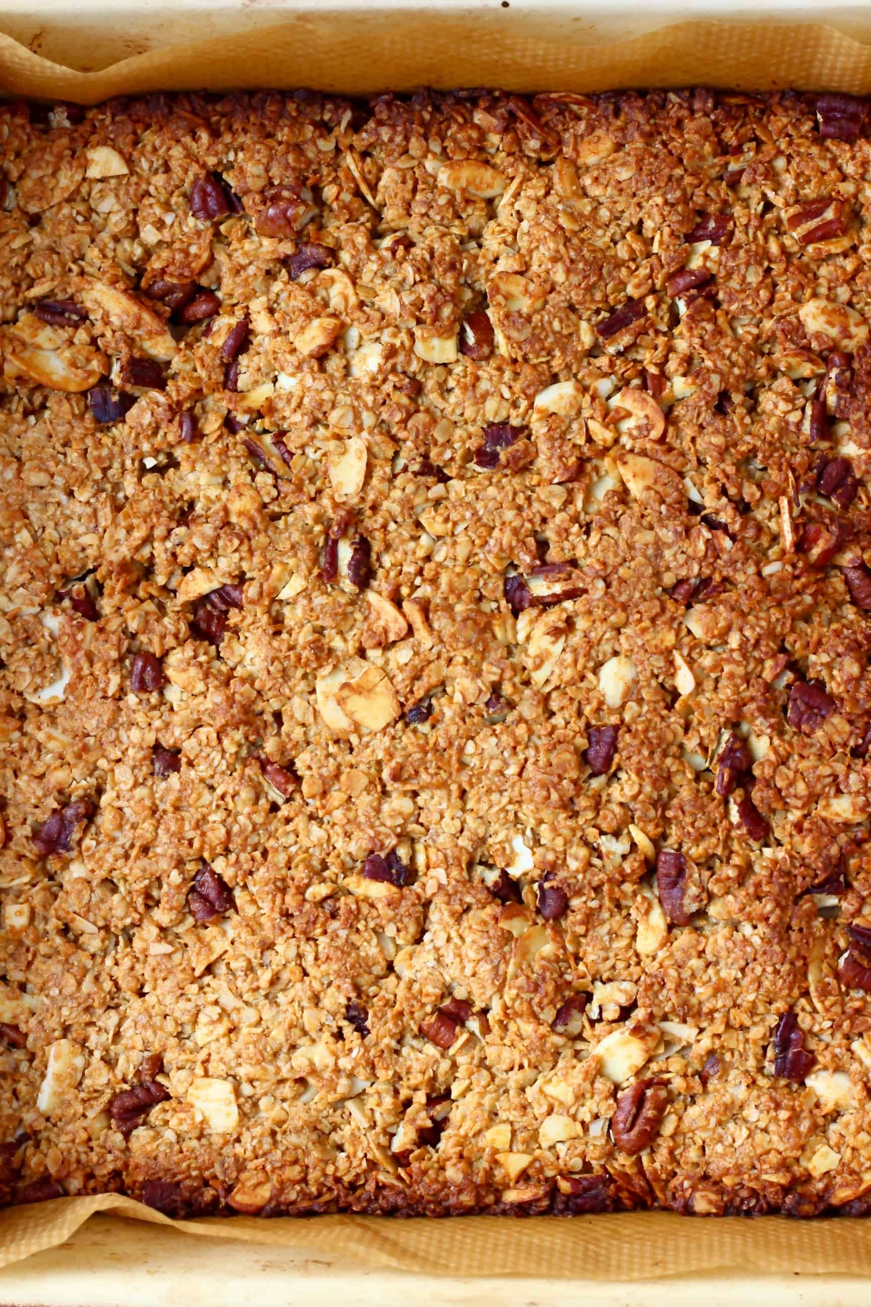 Baked vegan granola bars in a square baking tin lined with baking paper