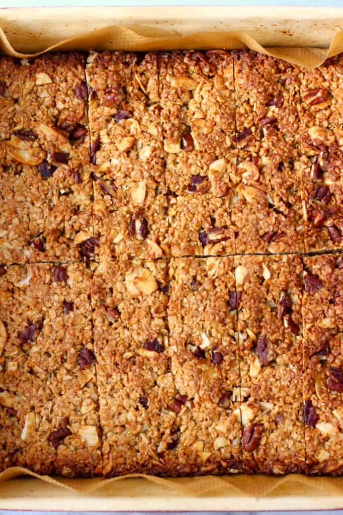 Baked granola bars in a square baking tin lined with baking paper against a marble background