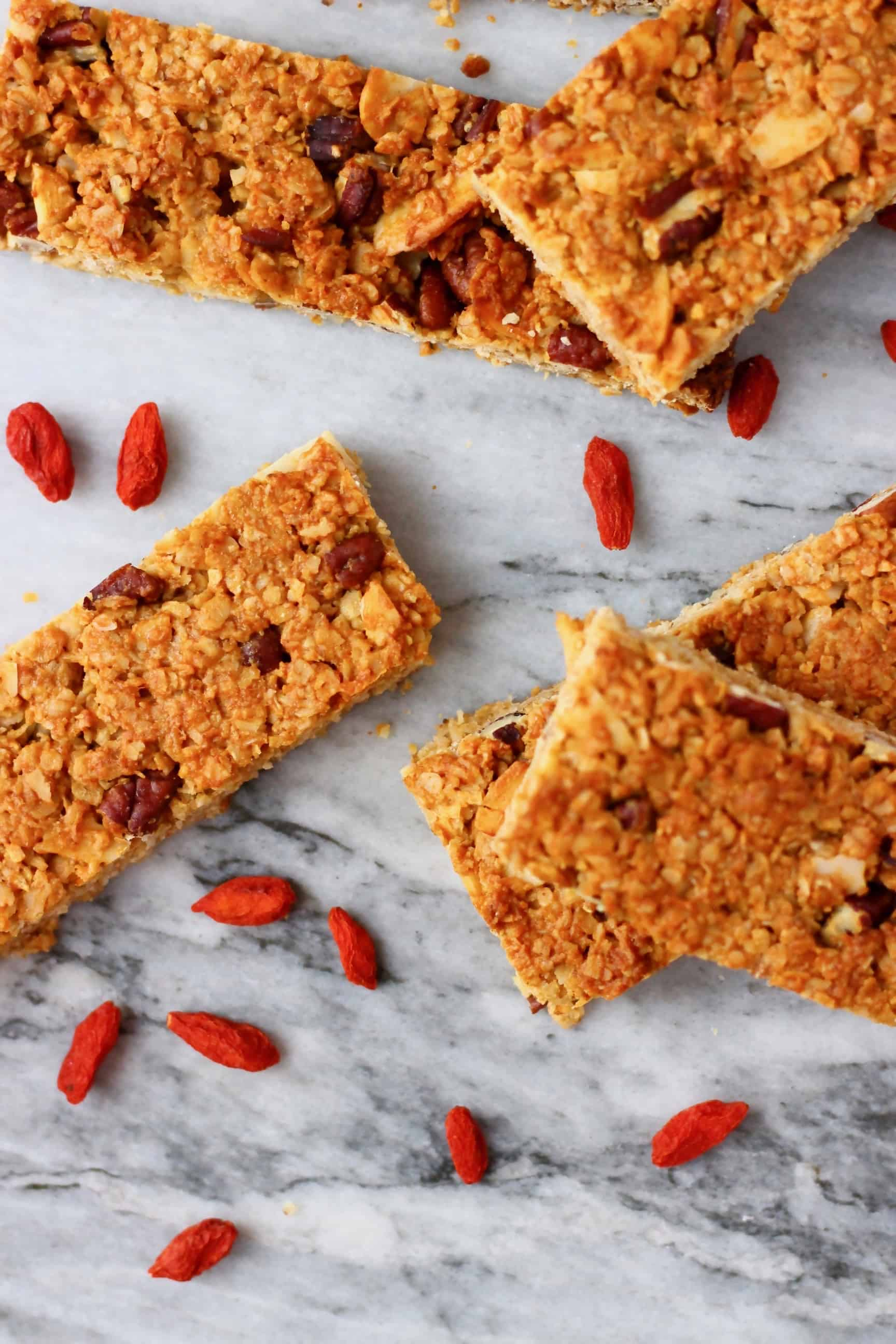Five vegan granola bars on a marble background