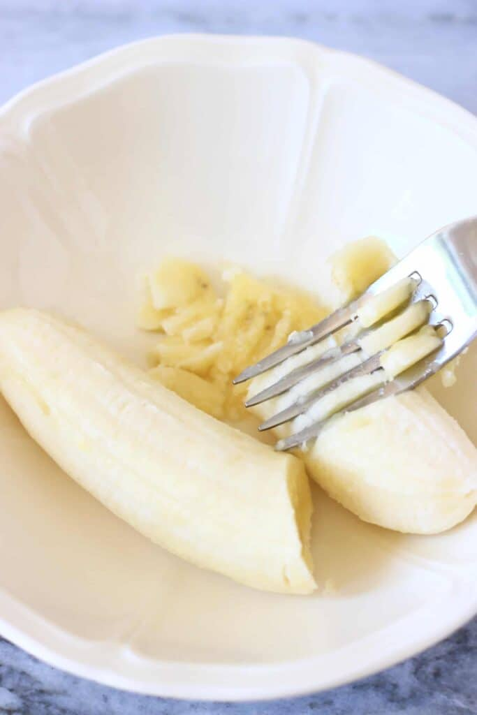 Photo of a banana in a white bowl being mashed with a silver fork against a marble background