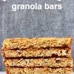 A stack of five granola bars on a marble slab against a grey background